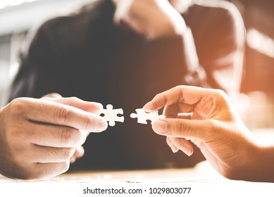 Hands fingers businessman team work holding and join pieces two jigsaw connecting couple puzzle piece for matching to goals target, success and start up new project in office.  Business Concept.