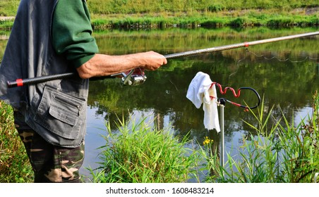 Hands of a fisherman hold a fishing rod at the river at Cluj-Napoca, Romania on September 9, 2014.