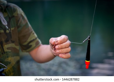 the hands of the fisherman on fishing wear a worm on the hook and hold the feeder with fish food