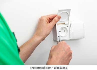 Hands fixing a socket with a screwdriver