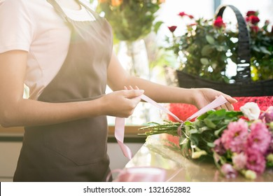 Hands of florist in apron tying up silk ribbon around bouquet of fresh pink and white flowers during work