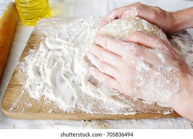 Hands in flour closeup kneading dough