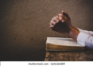 Hands folded in prayer on a Holy Bible in church concept for faith, spirituality and religion, woman praying on holy bible in the morning. woman hand with Bible praying. - Shutterstock ID 1641364489