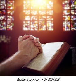 Hands folded in prayer on a Holy Bible in church concept for faith, spirituality and religion