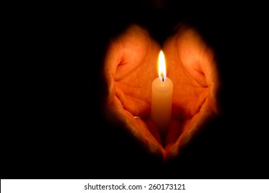 Hands folded in the shape of heart holding a burning candle on dark background with place for your text