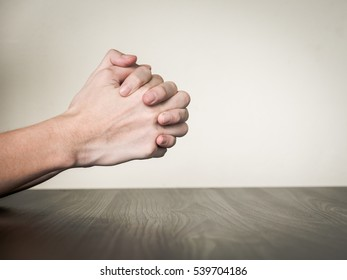 Hands folded together on the table, praying concept