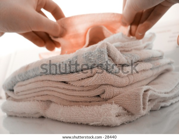 Hands folding laundry, atop a pile of folded towels. Focus on pile of towels. High key.