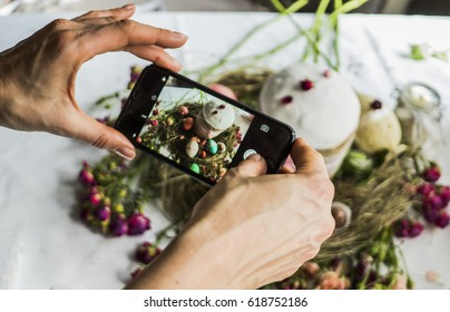 hands of food bloger shooting easter composition by smartphone