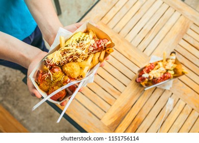 Hands of a Food hunter holding a craft tray with street fast food on the background of a wooden table. Sausage, cheese, potatoes, sauce in a kraft plate. Street European fast food.