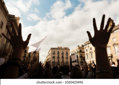 hands in the foreground and back lit people demonstrating massively with flags and white banners through the streets of a European city