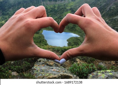 Hands in the form of a heart and on the background a lake in the form of a heart in the mountains