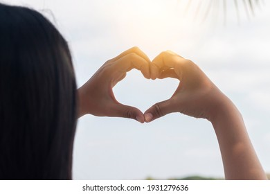 Hands in form of heart shape on blue sky background.Valentine concept