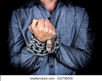 Hands of a formally dressed man chained with an iron chain and a padlock (on a black background)