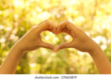 hands forming a heart shape with bokeh background
