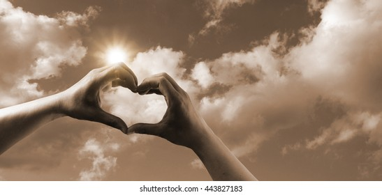hands are forming heart symbol for love in sepia with sunlight