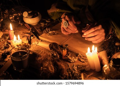 Hands fortune teller over an ancient table with herbs and books. Manifestation of occultism in the form of divination.