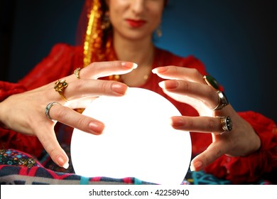 hands of a fortune-teller working with a shining crystal ball