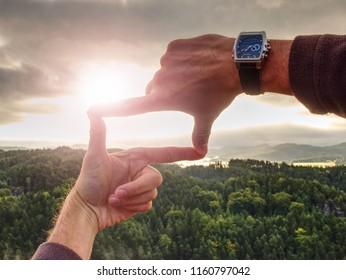 Hands framing view distant over sunset, vintage filter. . Close up of hands making frame gesture.