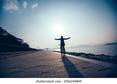 Hands free cycling cyclist riding bike in the sunrise coast road