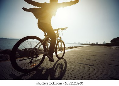 Hands free cycling happy cyclist riding bike in the sunrise coast