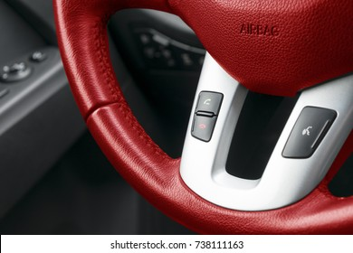 Hands free and media control buttons on the red steering wheel in black leather, modern car interior details