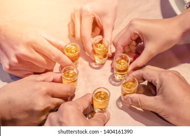 Hands of friends with glass Cheers clinking whisky drink in party.