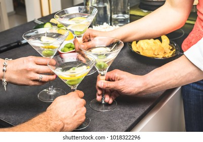 Hands of friends having fun at house party with pre dinner aperitif martini cocktails and chips olives snacks - Young people spending time together at home - Birthday event celebration concept