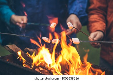 Hands of friends roasting marshmallows over the fire in a grill closeup
