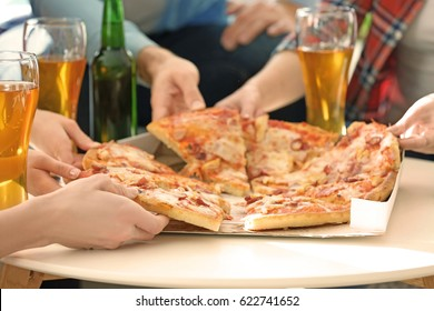 Hands of friends taking slices of tasty pizza from cardboard box at home party