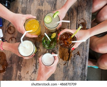 Hands of friends together in circle holding the different cocktails with ice on background of the old wooden table surface