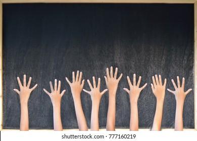 Hands in front of a blackboard .Education ,preschool ,kids concept.