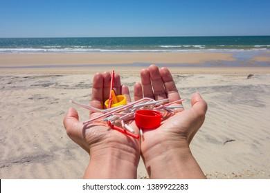 Hands full of plastics on the beach. straws, ear swabs, plugs, lollipops sticks... Plastic pollution concept.
