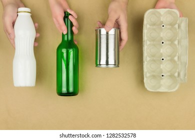 Hands with garbage trash: metal aluminium can, disposable plastic bottle, glass bottle and paper egg tray isolated on brown background. Green environment, reuse, refuse and recycle concept.