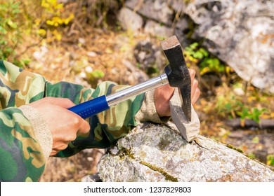 hands of a geologist splitting a mineralogical sample with a geological hammer