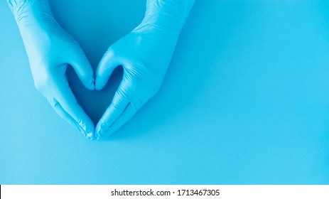 hands gesture of doctor wearing blue gloves on blue background, heart shape sign for love