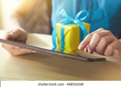 hands with gift box and digital tablet