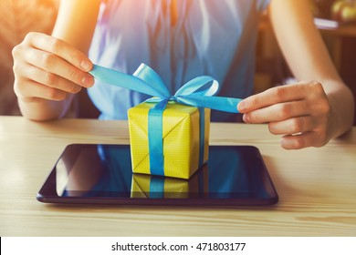 hands with gift box and digital tablet. online shopping concept