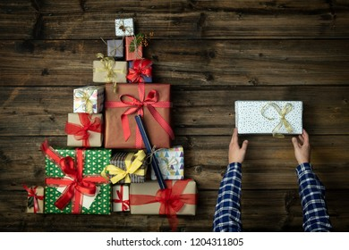 Hands with gift present box in vertical top view dark vintage wood with christmas tree pine made of gift present boxes.Xmas winter holiday season party social media card background,portrait story