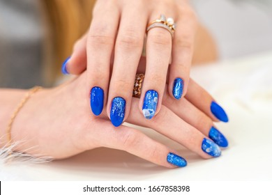 Hands of a girl with a beautiful blue manicure are on display. blue glossy nail Polish on the hands. Light background. Hands are on the table. Example of a manicure with the theme of space.