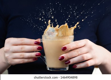 In the hands of the girl a cup of coffee with milk. Coffee spray. Splash Beautiful shapes from coffee splashes. Red manicure. Close-up. Breakfast time. Concept