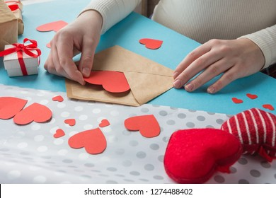 hands of the girl prepare a gift for Valentine's Day, handmade Valentines on a blue background