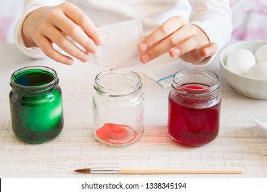 The hands of a girl preparing and decorating easter eggs
