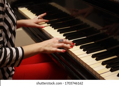 Hands of a girl with red nails on the piano keys