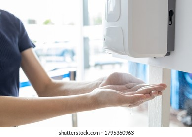 Hands of girl using automatic alcohol gel dispenser,spraying on hands,clean hands with alcohol hand sanitizer machine,antiseptic, disinfectant to kill germs,new normal life under Coronavirus,COVID-19
