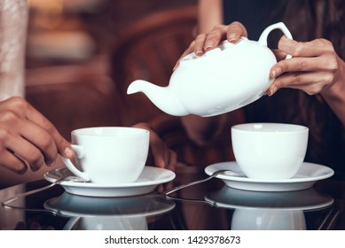 Hands of Girls Pouring Tea Into Cups. Women Has Five Oclock Tea. Female Friends Sitting in Retro Cafe.