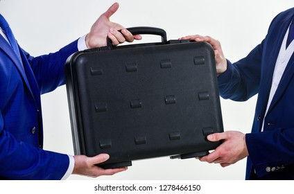Hands give briefcase for exchange or offer bribe. Business transfer concept. Male hand hold briefcase. Handover of case in hands of business partners. Handover of illegal goods. Illegal deal handover.