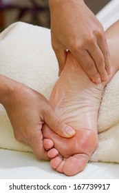 hands giving a foot massage with a white towel on the background