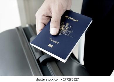 Hands giving passport (of Australia) - dark tone
