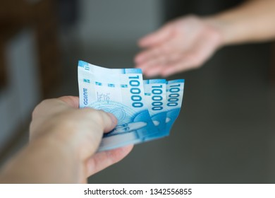Hands giving and receiving chilean money notes. Chile ten thousand (10000) pesos. Selective focus.