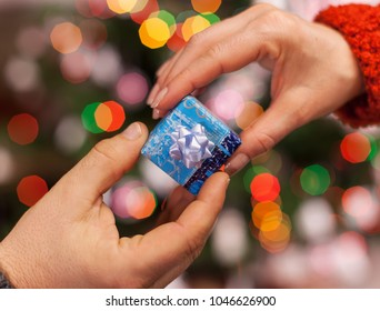 Hands giving and receiving small gift package on colorful blurry lights background - christmas  and holiday season, shallow depth